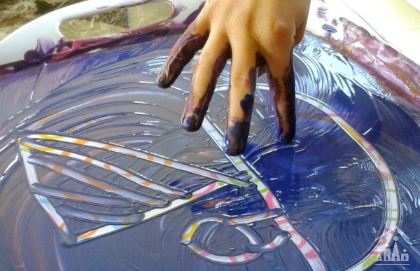 Child finger painting a boat