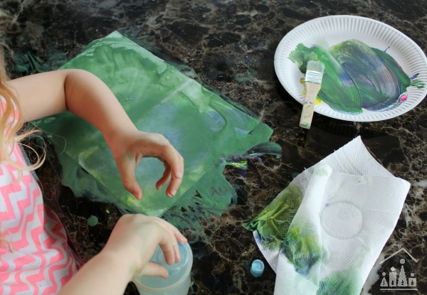 Preschooler creating a messy painting with water