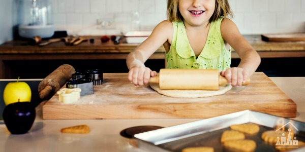 Girl rolling out pastry helping out in the kitchen