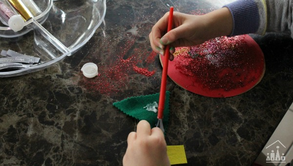 Gluing a felt christmas tree decoration