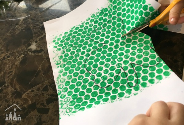 Cutting out a Bubble Wrap Shamrock Man