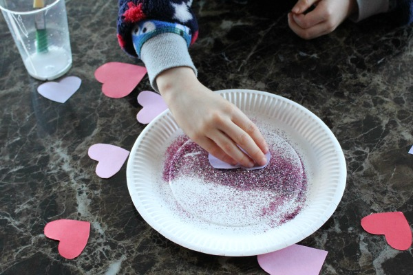 Covering hearts in glitter for a valentines day collage