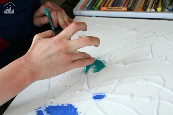 Child blending pastels on a glue resist art project