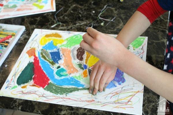 Child peeling glue off a glue resist art project