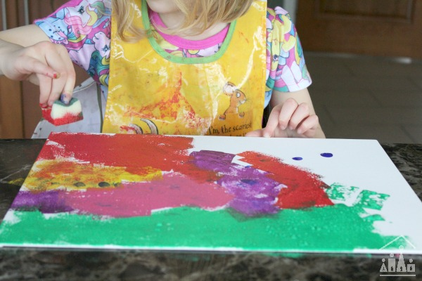 Child sponge painting on a piece of canvas