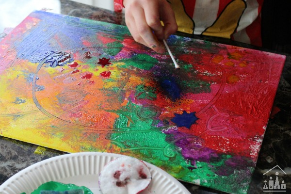Child artist using q-tips on canvas