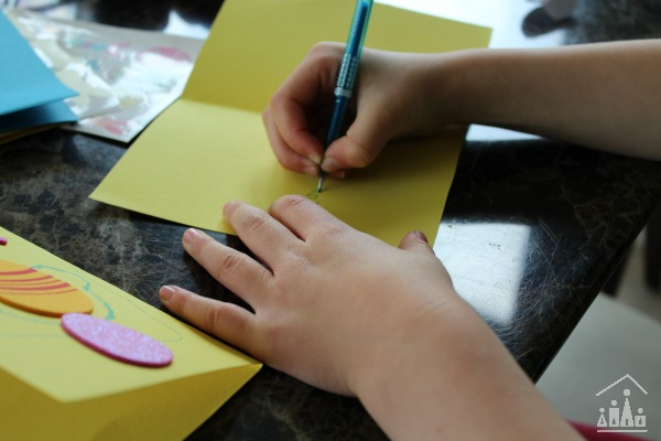 Kids using Easter stickers to decorate cards